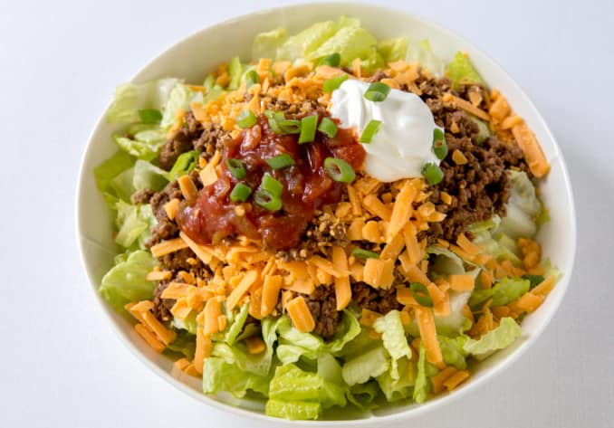 keto salad bowl filled with lettuce, ground beef, cheese, salsa, and sour cream