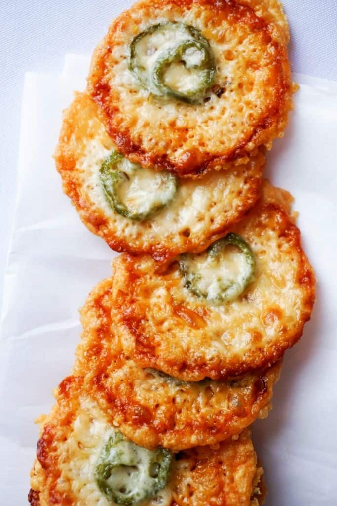 row of parmesan crisps with a single slice of jalapeno baked into each