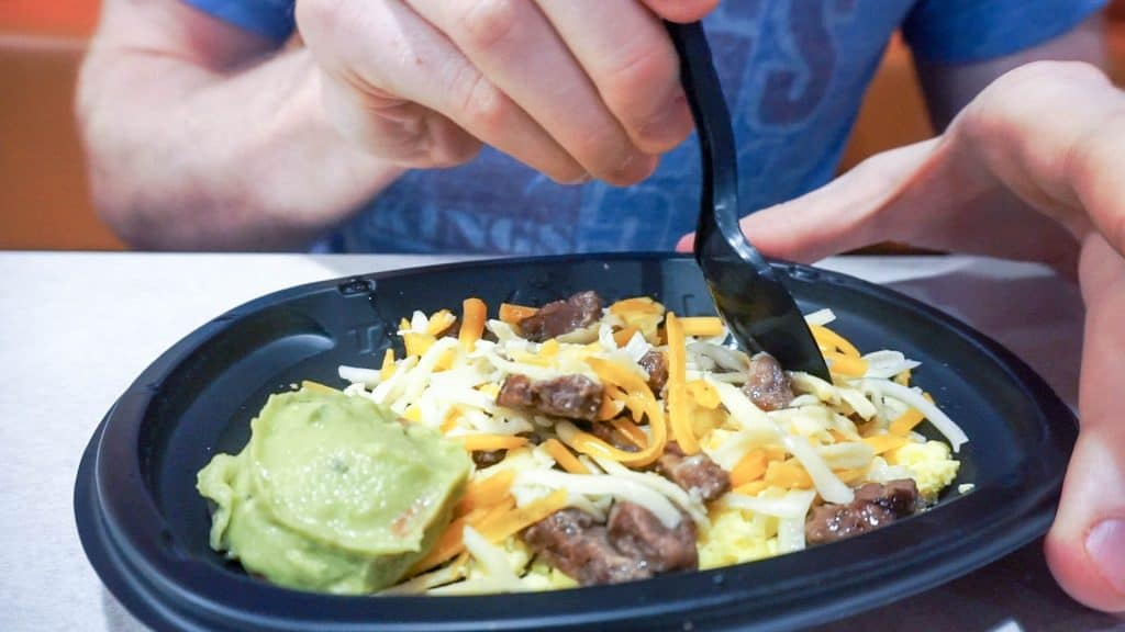 taco bell meal in a take out container being eaten with a spork