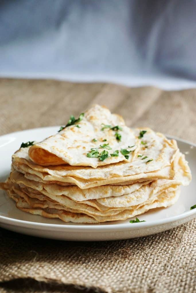 stack of 15 low carb tortillas with the top one folded and topped with cilantro