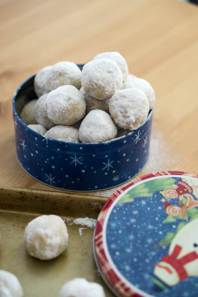 A tin of snowball cookies atop a wood cutting board