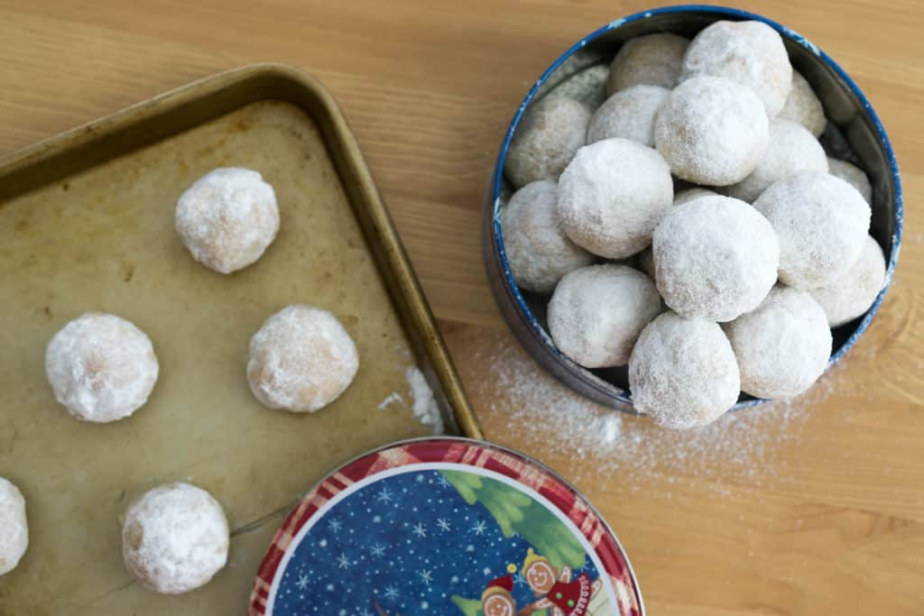 Walnut snowball cookies in a tin next to a baking sheet