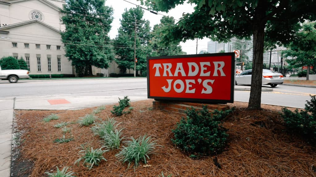 trader joes sign outside of store on a busy street