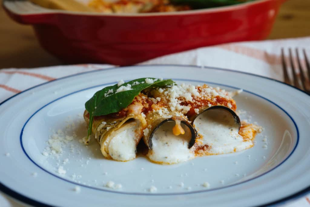 eggplant manicotti being plated and served