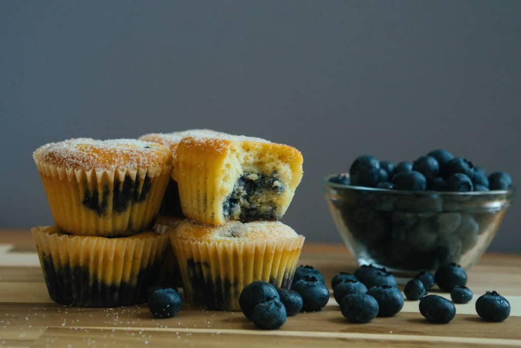 blueberry muffins on a cutting board next to a bowl of blueberries