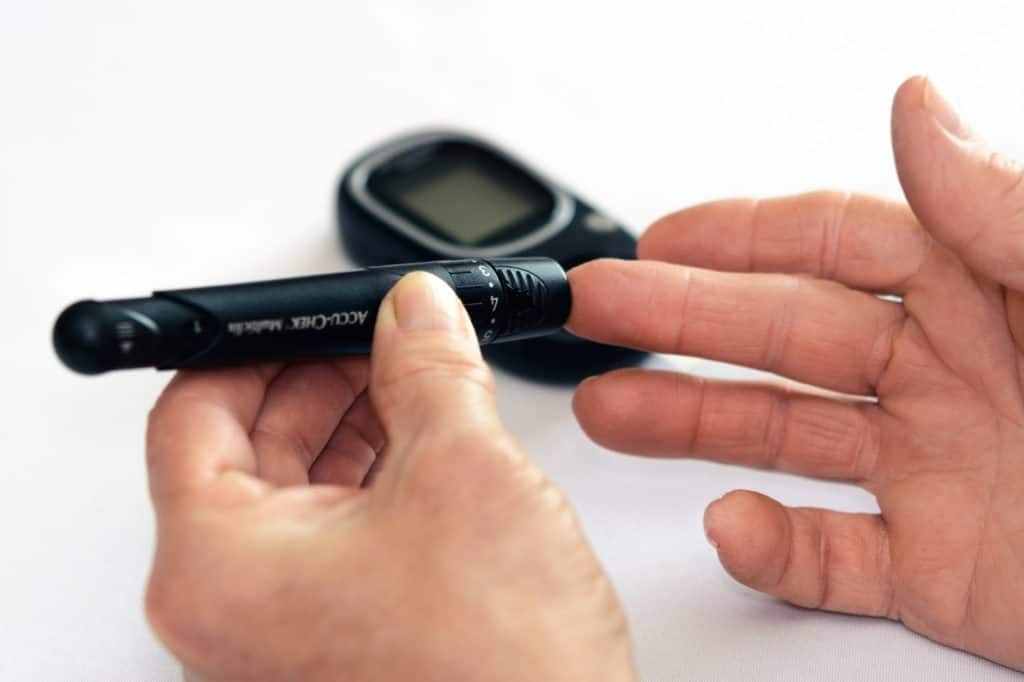 close up image of a man poking his finger with a glucose testing device to test his blood sugar