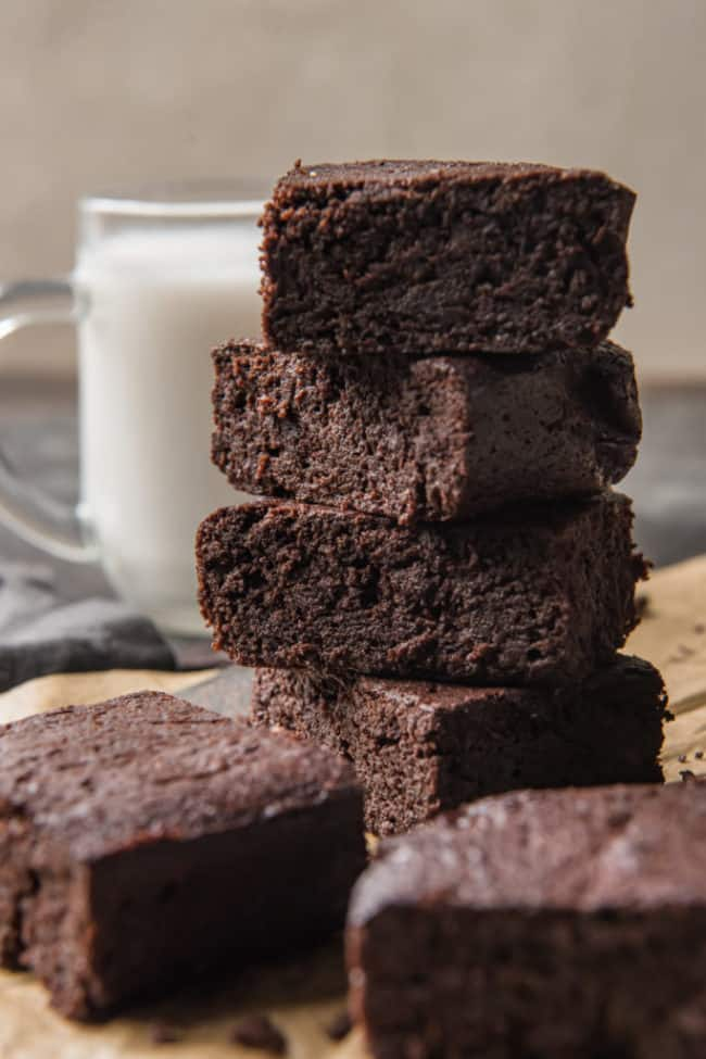 keto brownies stacked with other brownies in the foreground and a glass of milk nearby