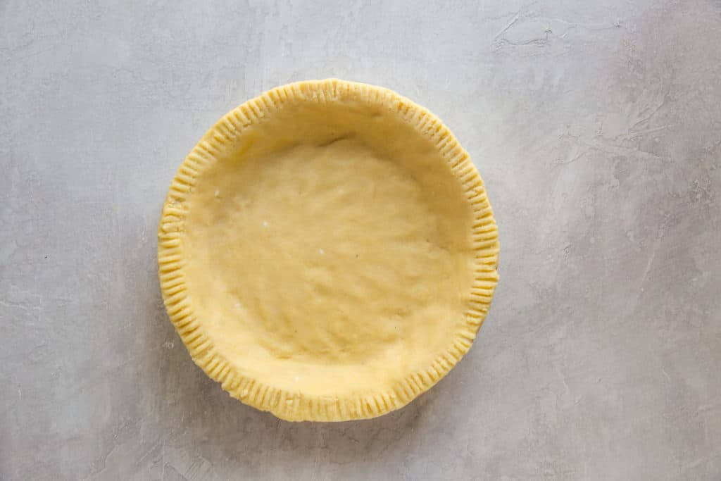 keto pie crust before being baked formed into a large pan sitting on the counter top