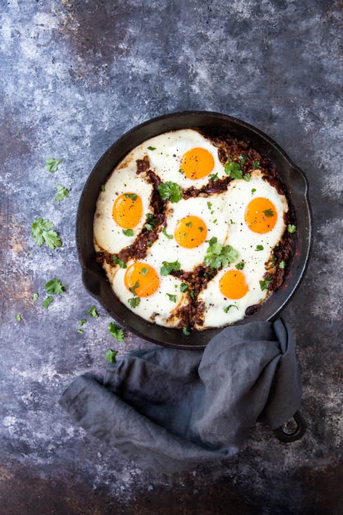 The masala baked Indian eggs cooked in a cast iron skillet with a hand towel covering the handle