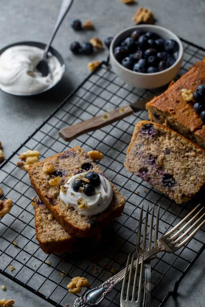 Sliced poundcake surrounded by cream and blueberries
