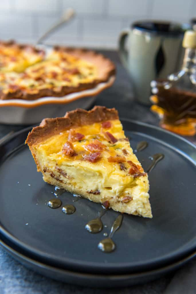 A slice of the bacon and cheese keto quiche served on a black plate drizzled with maple syrup