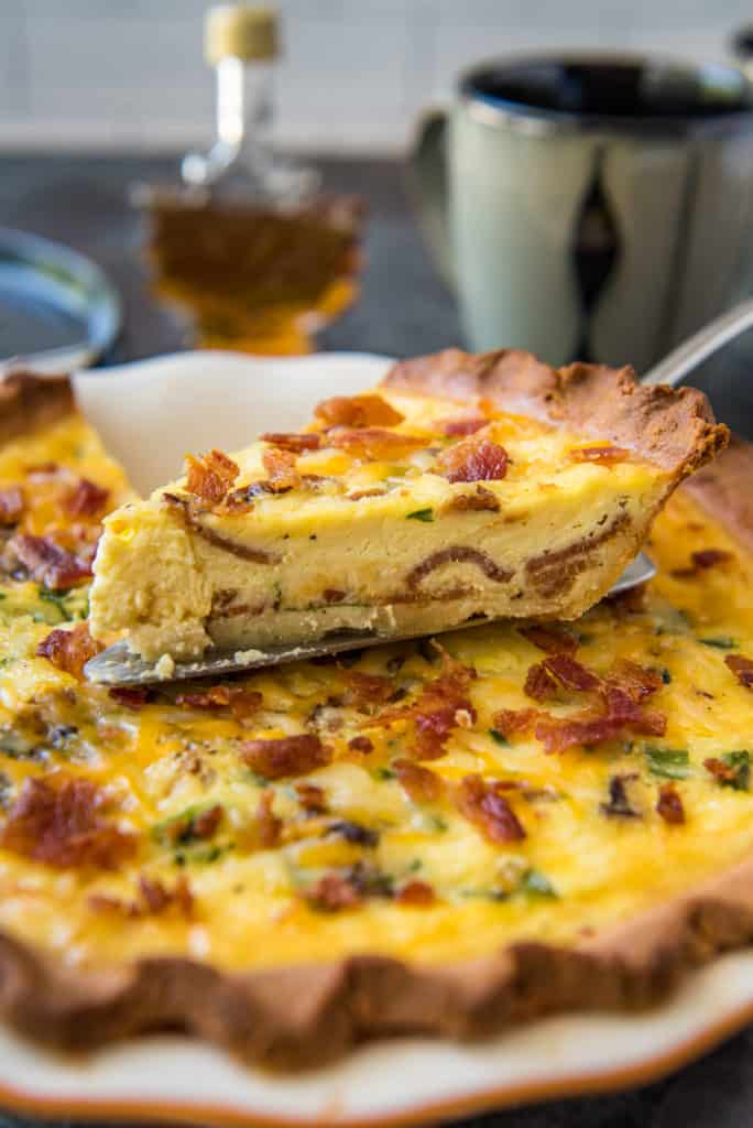 keto quiche being sliced and served with maple syrup and a cup of coffee
