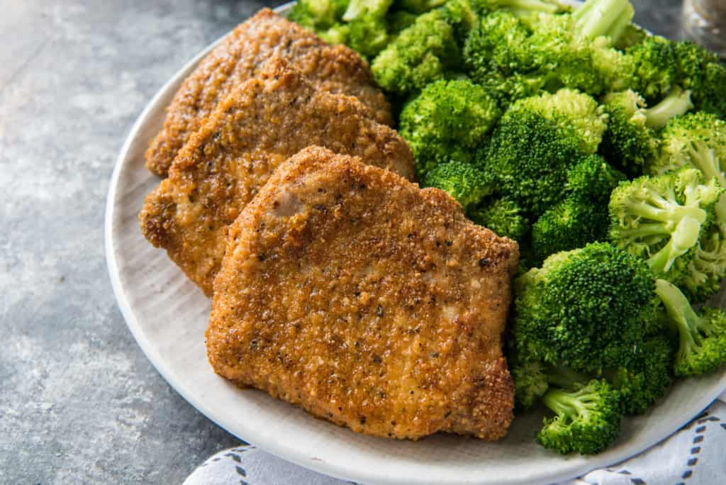 Three air fryer pork chops served with broccoli on a white plate on top of a white and gray kitchen towel