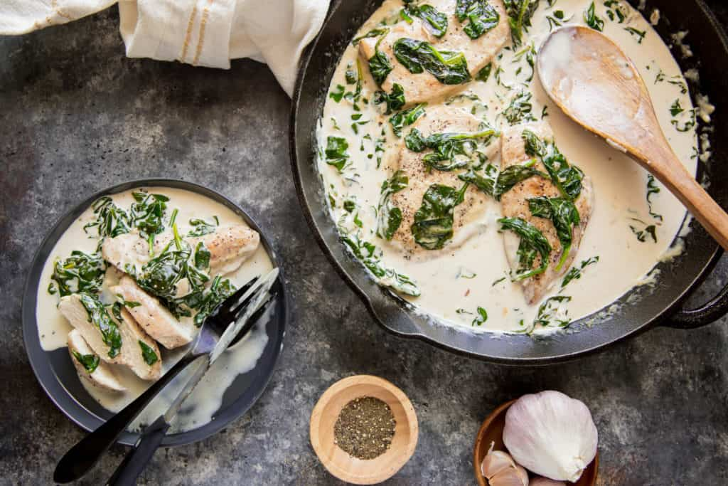 A large cast iron skillet filled with chicken and spinach florentine with a wooden spoon in it and a plate of the chicken and spinach florentine cut up with a knife and fork, a side of black pepper and a garlic bulb