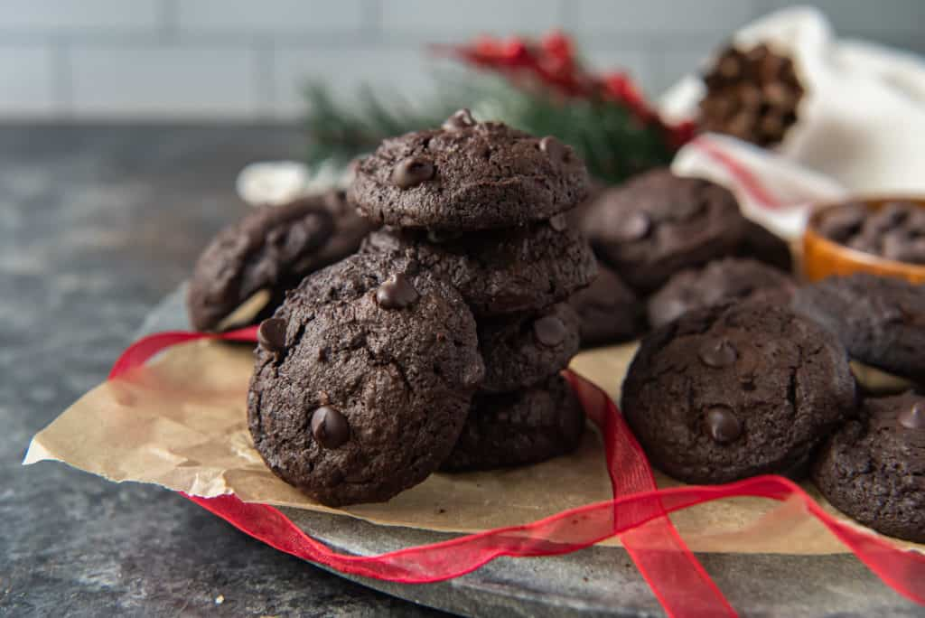 A pile of keto chocolate cookies on brown parchment paper surrounded by red ribbon