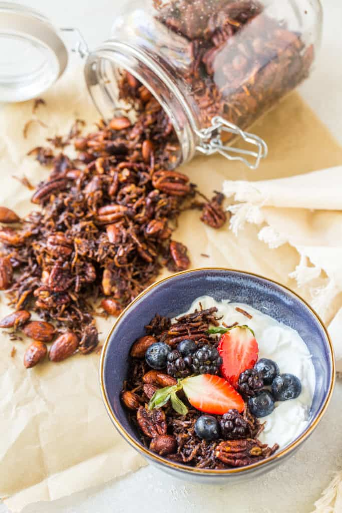 A bowl of yogurt topped with keto granola and berries - eggless recipe