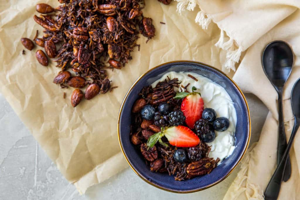 A blue bowl filled with yogurt, keto granola and berries with two spoons and some granola spilled out on parchment paper behind it