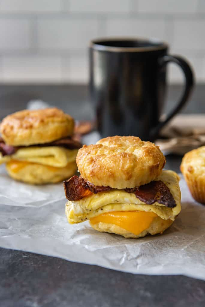 breakfast biscuit sandwich with coffee cup in background
