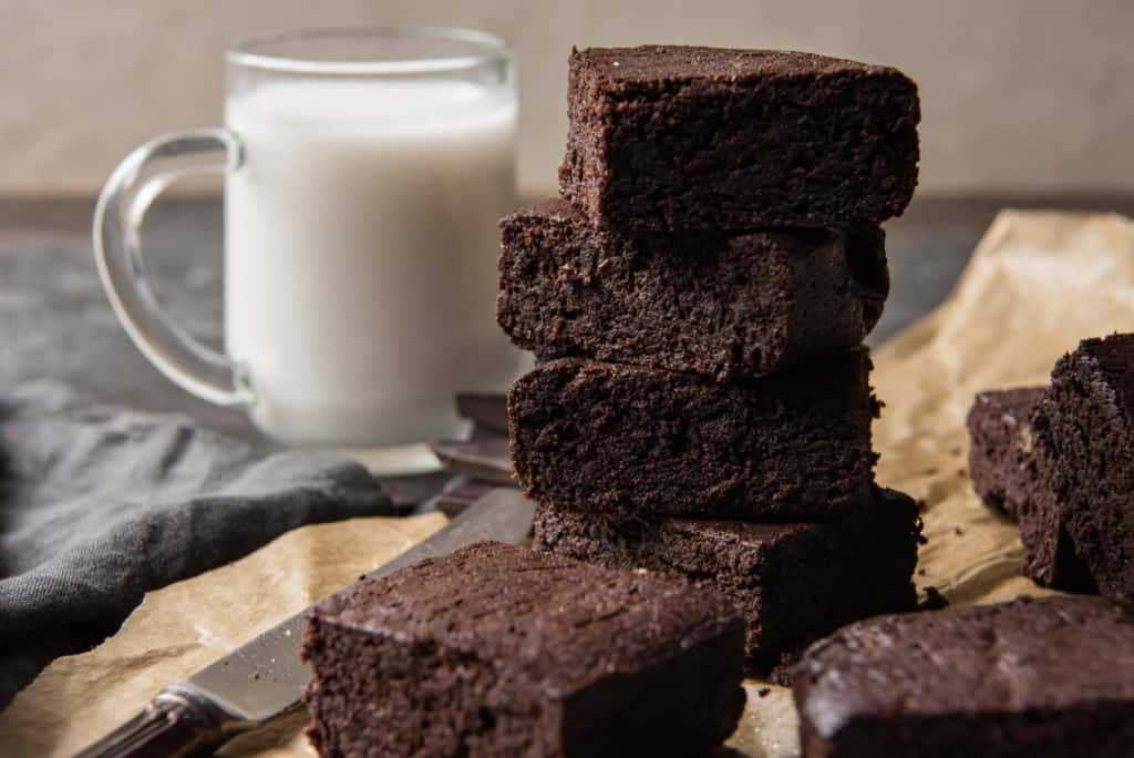 stack of fudgy brownies on brown parchment paper with a small glass of milk