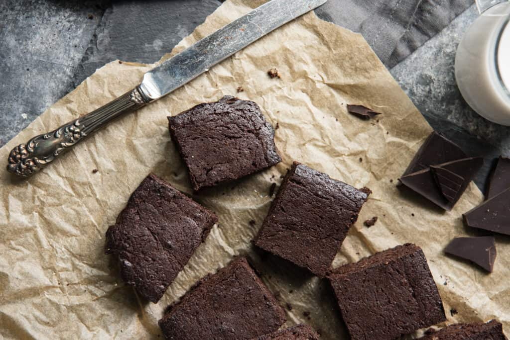 keto brownies cut and placed on parchment paper with a butter knife.