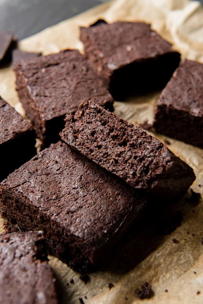 close up picture of sliced brownies loosely arranged on a piece of brown parchment paper