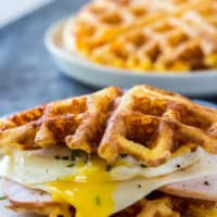 keto chaffles sandwich made with ham and an over easy eagg with a stack of chaffles behind