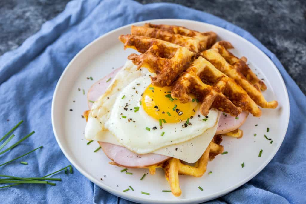 a keto chaffles sandwich using ham and a sunny side up egg on a blue table cloth