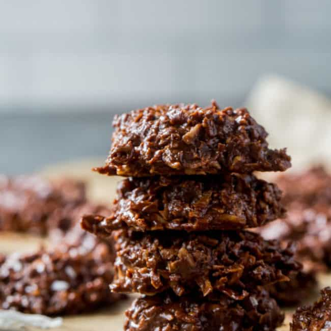 chocolate keto no bake cookies stacked on top of each other with pecans in the background