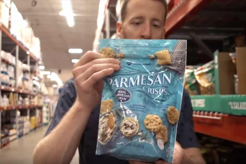 A man holding a large bag of Parmesan Crisps at Sam's Club.
