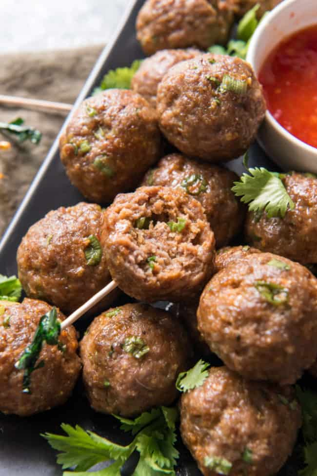 meatballs on a rectangle plate with a bite out of one of them