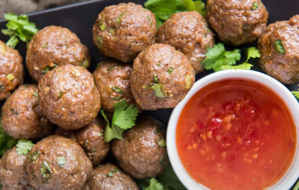 Overhead close up of Meat Balls with a cup of Marinara sauce next to them.