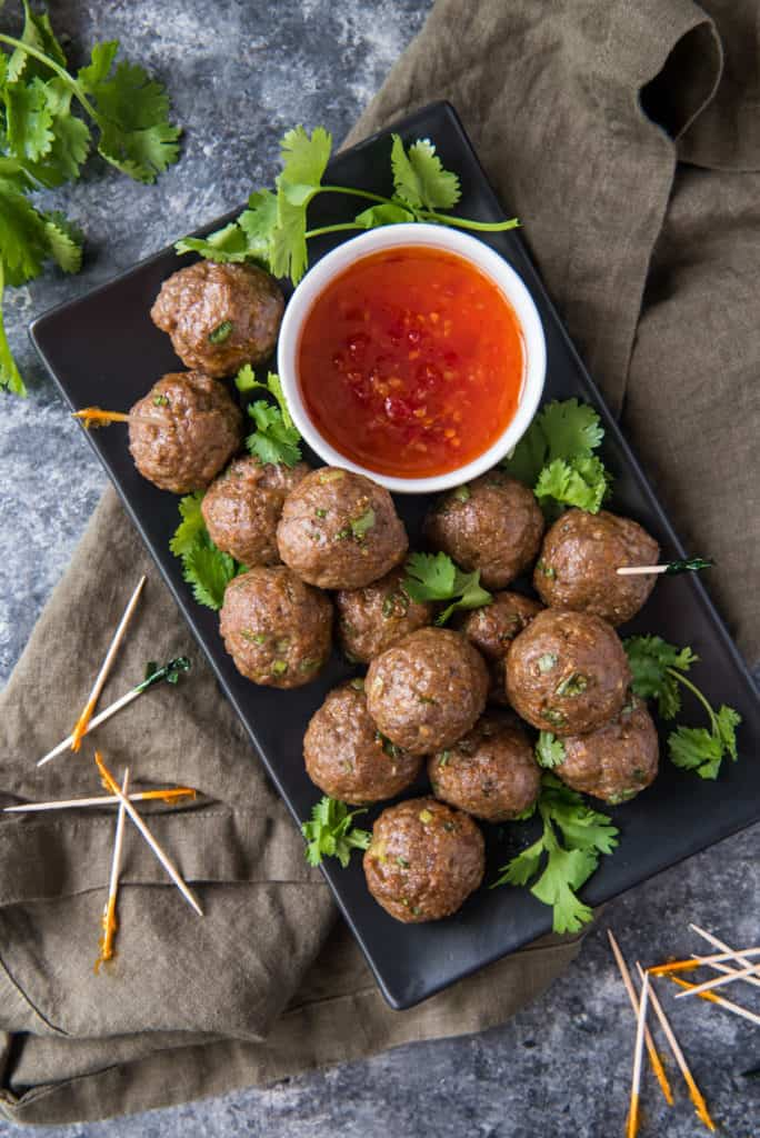 air fryer meatballs on a black tray next to dipping sauce and toothpicks