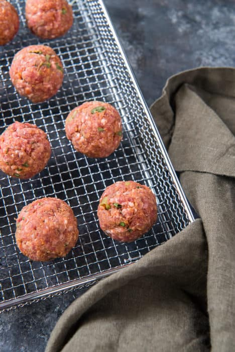 Raw, formed air meatballs evenly placed on a metal frying basket with a kitchen towel on the right side