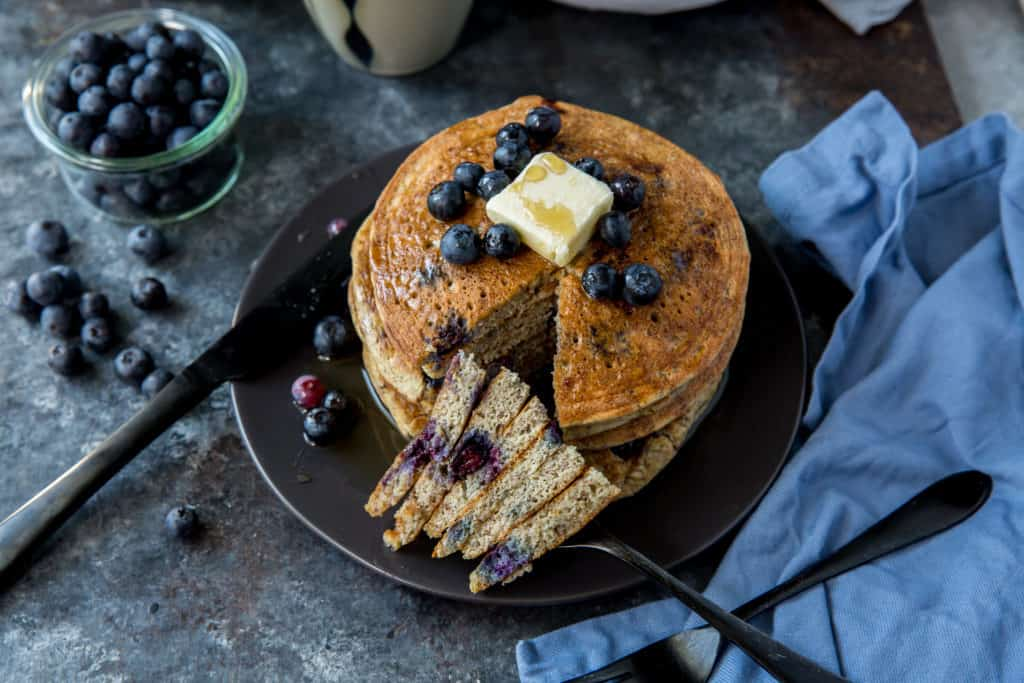 A stack of blueberry keto pancakes on a black plate topped with butter and blueberries and a triangular stack cut out with a fork in it served with a bowl of blueberries to the left
