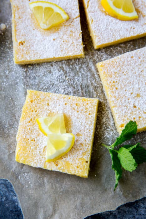 four pieces of keto lemon bars on parchment paper topped with lemon slices, mint and powdered sugar