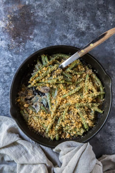 low carb green bean casserole in a cast iron skillet with a serving spoon and gray kitchen towel