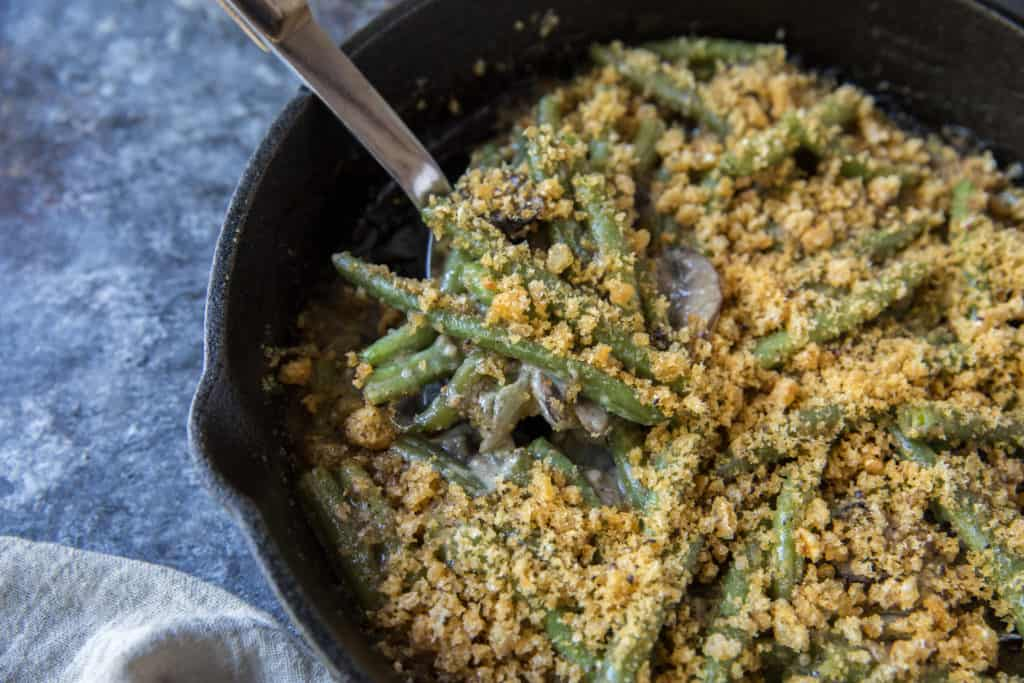 low carb green bean casserole in a cast iron skillet with a serving spoon