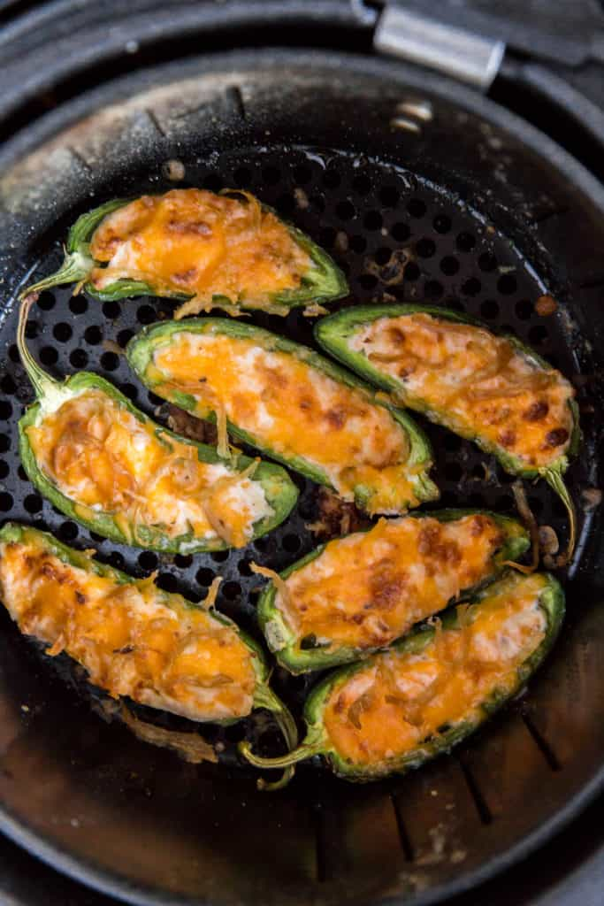 seven cooked air fryer jalapeno poppers in the air fryer basket