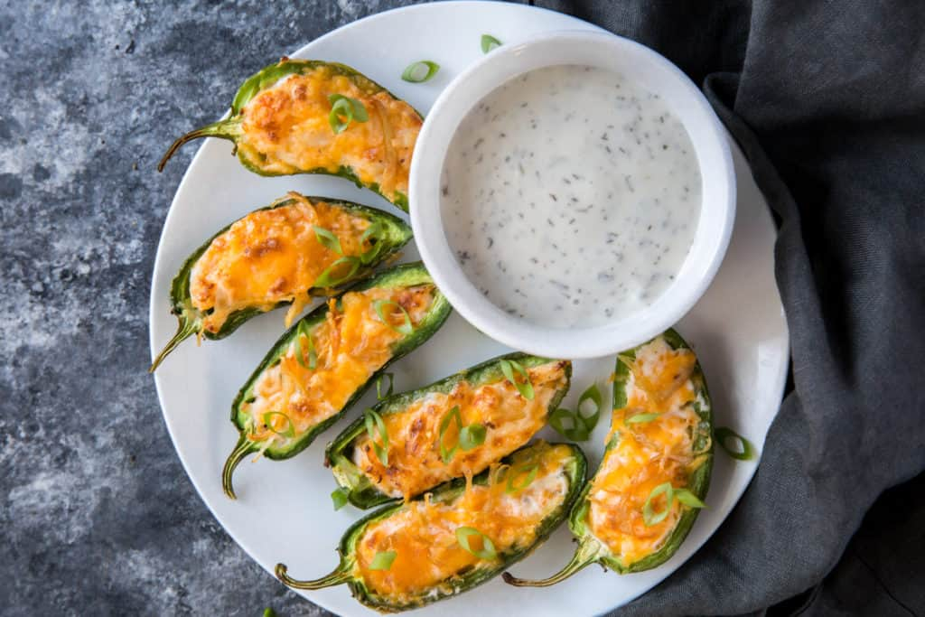 jalapeno poppers on a plate with a side of dipping sauce