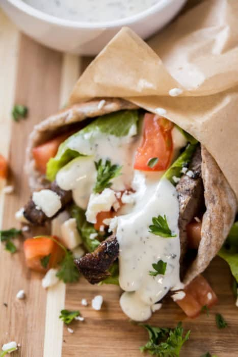 one healthy gyros recipe wrapped in parchment paper and topped with tzatziki sauce