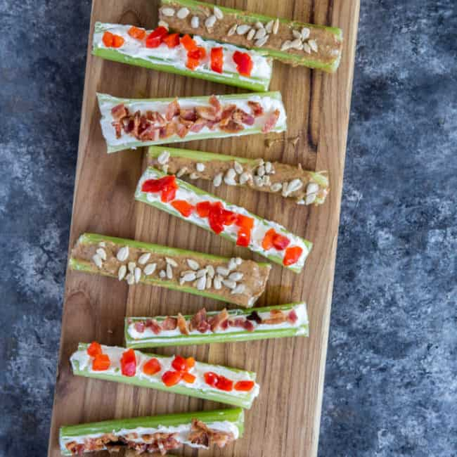 Stuffed celery three ways displayed on a wood cutting board