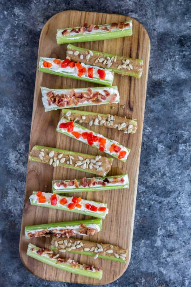 Stuffed celery three ways displayed on a wood cutting board