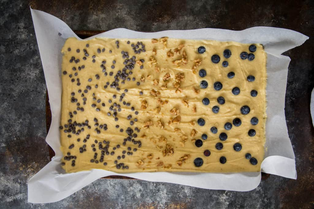 a parchment paper line sheet pan with pancake batter, blueberries, pecans and sugar free chocolate chips on top