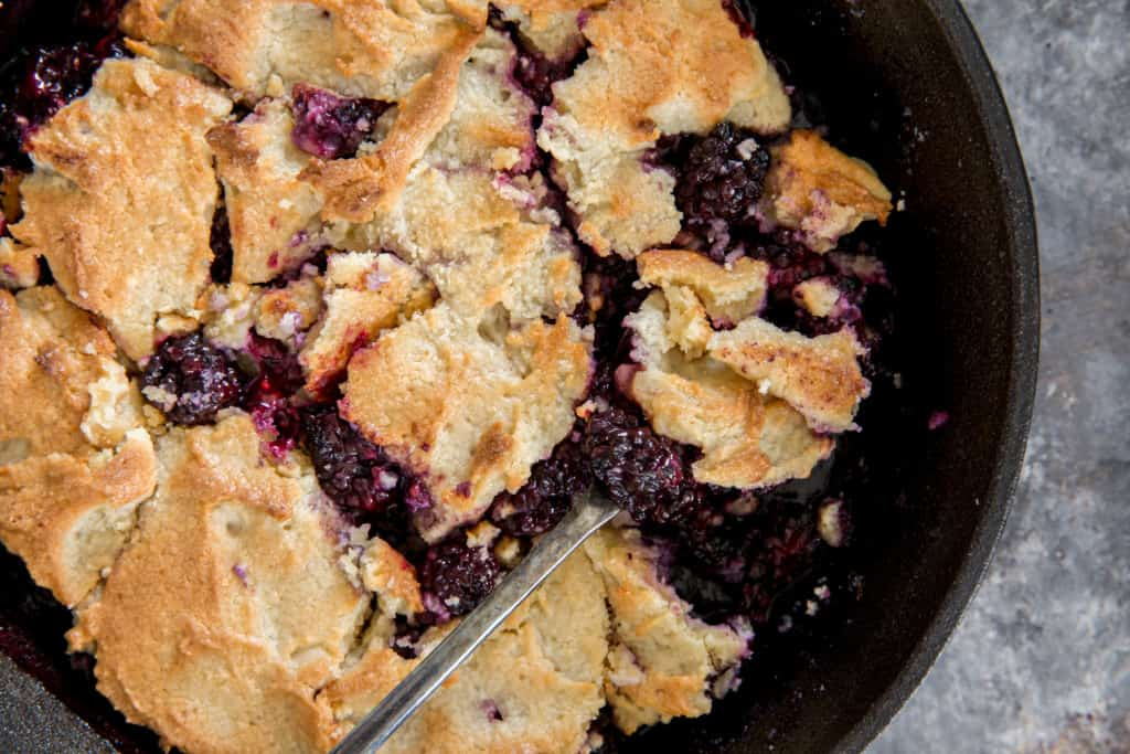 keto blackberry cobbler baked in a cast iron skillet with a spoon