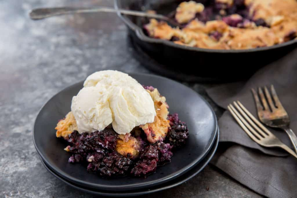 keto blackberry cobbler served on a black plate with a scoop of vanilla ice cream on top