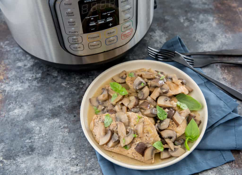 Instant pot chicken marsala served on a white plate with an instant pot in the background