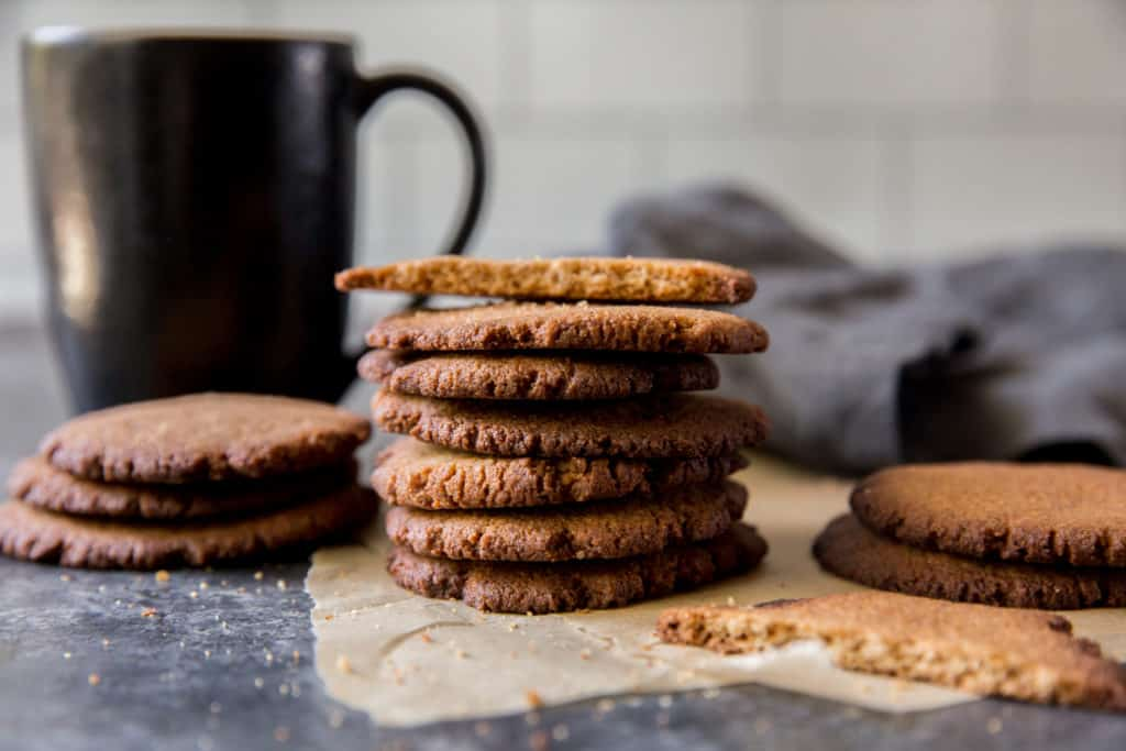 three stacks of keto ginger cookies with a coffee mug in the background