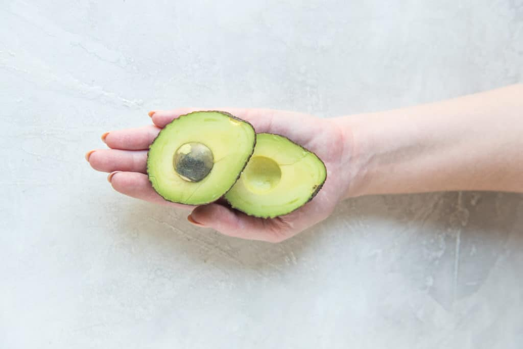 sliced avocado in the palm of a hand