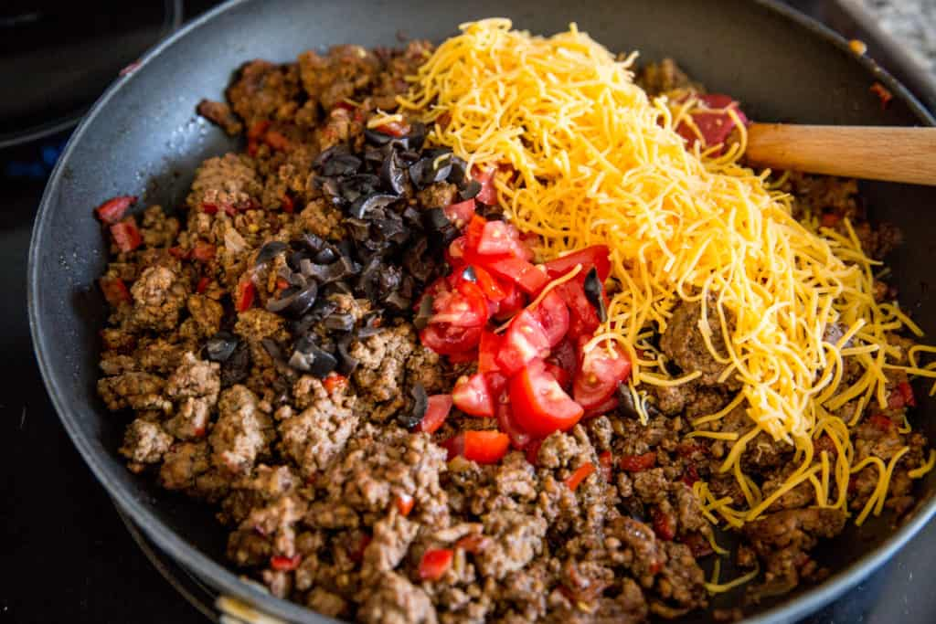 ground beef, olives, tomatoes and cheese cooked in a skillet for a keto taco salad casserole