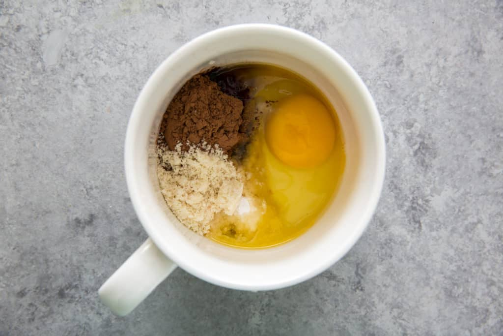a white mug filled with an egg, cocoa powder and almond flour to make a keto chocolate mug cake
